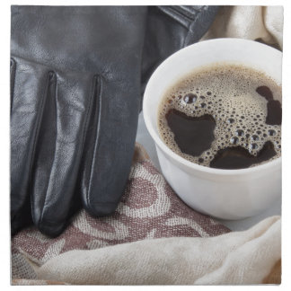 View close-up on white cup of coffee and gloves cloth napkin