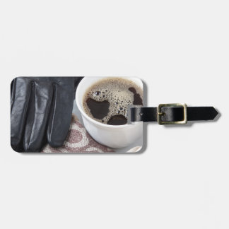 View close-up on white cup of coffee and gloves luggage tag