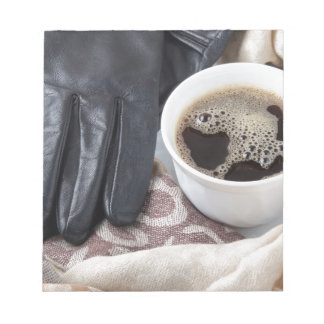 View close-up on white cup of coffee and gloves notepad