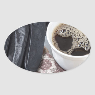 View close-up on white cup of coffee and gloves oval sticker