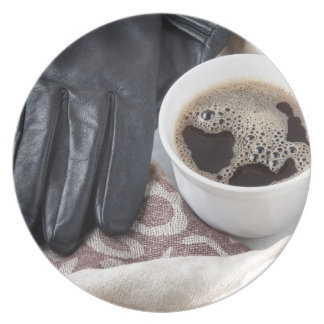 View close-up on white cup of coffee and gloves plate