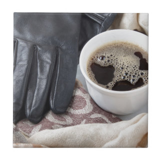 View close-up on white cup of coffee and gloves tile