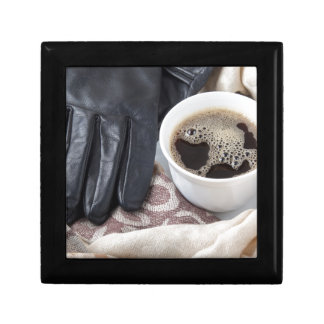 View close-up on white cup of coffee and gloves trinket box