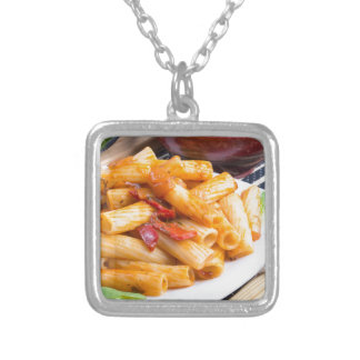 View closeup on a dish of rigatoni pasta silver plated necklace