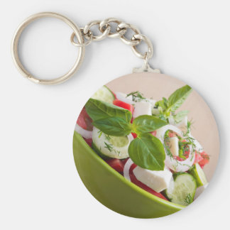 View closeup on a green bowl with a useful salad basic round button keychain