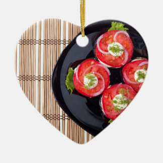 View from above on a dish with fresh sliced tomato ceramic heart ornament