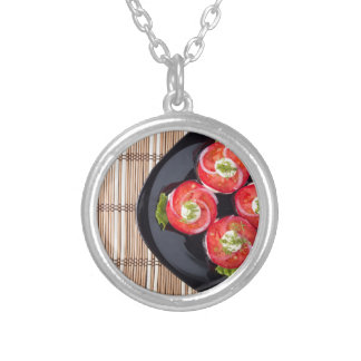 View from above on a dish with fresh sliced tomato silver plated necklace
