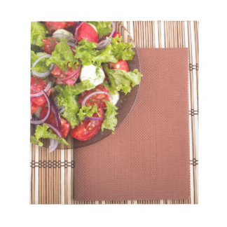 View from above on a plate with fresh salad notepads