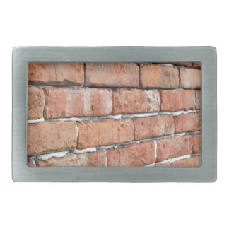 View of an old brick wall with a blur at an angle rectangular belt buckles