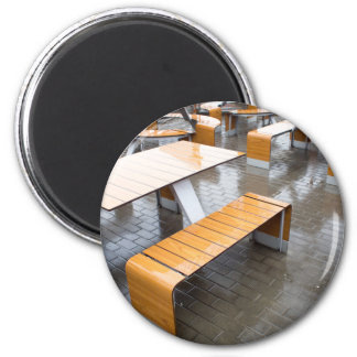 View of the outdoor cafe tables wet in the rain 2 inch round magnet