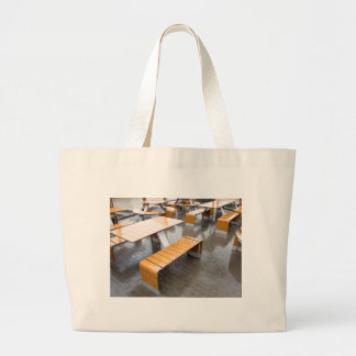 View of the outdoor cafe tables wet in the rain large tote bag