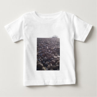 View over pebbles to silouetted West Pier Baby T-Shirt