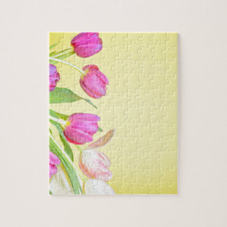 View to the multicolored tulips over yellow paper puzzle