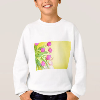 View to the multicolored tulips over yellow paper sweatshirt