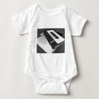 Vintage audio cassette tape on wooden table baby bodysuit