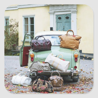 Vintage car with lots of luggage square sticker