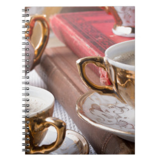 Vintage coffee cups with hot espresso and retro notebooks