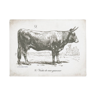 Vintage style cow on doormat with french writing.