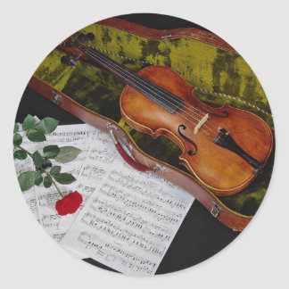 Violin and red rose on black background round sticker