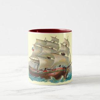 Voile vintage de bateau à travers la tasse bleue