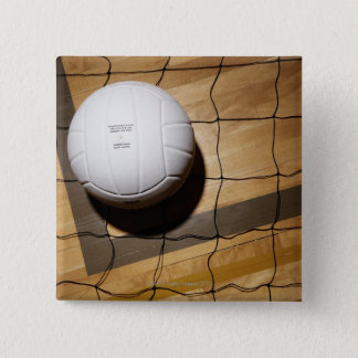 Volleyball and net on hardwood floor of 2 inch square button