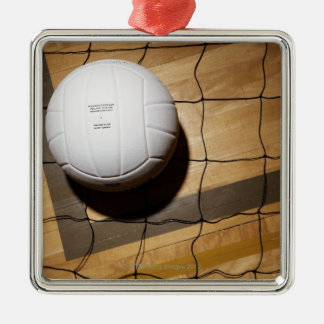 Volleyball and net on hardwood floor of metal ornament