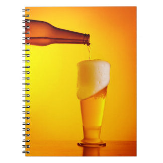 Waiter pouring beer, glass of a cold drink spiral note book