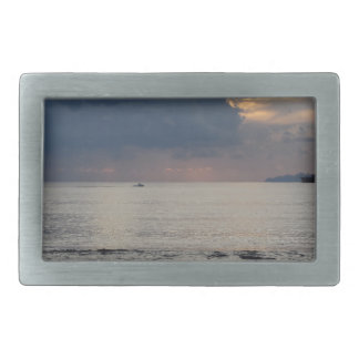 Warm sea sunset with cargo ship and a small boat belt buckle