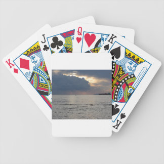 Warm sea sunset with cargo ship and a small boat bicycle playing cards