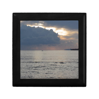Warm sea sunset with cargo ship and a small boat gift box