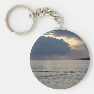 Warm sea sunset with cargo ship and a small boat keychain