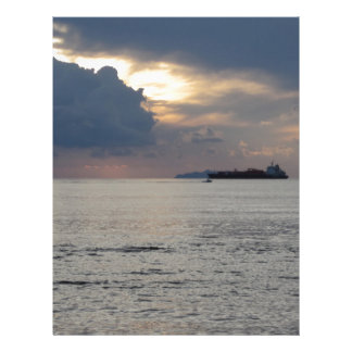 Warm sea sunset with cargo ship and a small boat letterhead