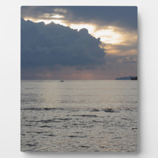 Warm sea sunset with cargo ship and a small boat plaque