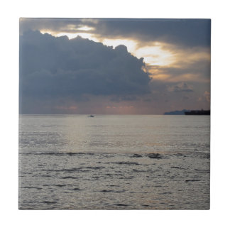 Warm sea sunset with cargo ship and a small boat tile