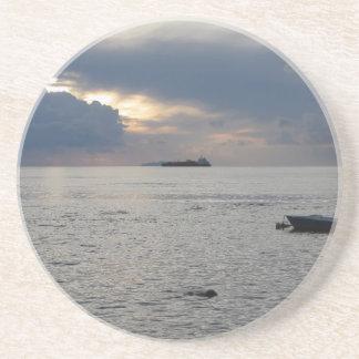 Warm sea sunset with cargo ship at the horizon coaster