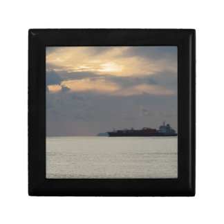 Warm sea sunset with cargo ship at the horizon gift box