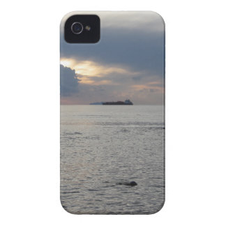 Warm sea sunset with cargo ship at the horizon iPhone 4 cases