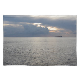 Warm sea sunset with cargo ship at the horizon placemat