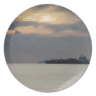 Warm sea sunset with cargo ship at the horizon plate