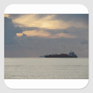 Warm sea sunset with cargo ship at the horizon square sticker