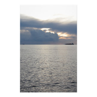 Warm sea sunset with cargo ship at the horizon stationery