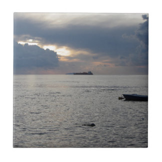 Warm sea sunset with cargo ship at the horizon tile
