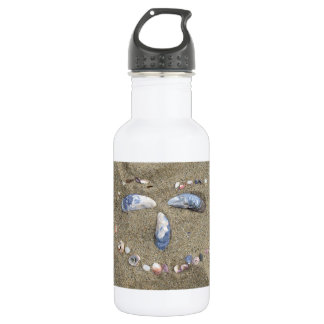 Water bottle face made in the sand with sea shells