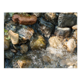 Water flowing over stones in a streambed postcard