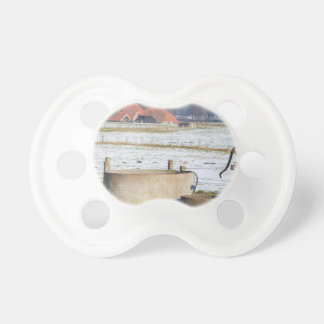 Water pump and well in winter snow landscape pacifiers
