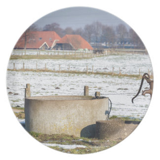 Water pump and well in winter snow landscape plate