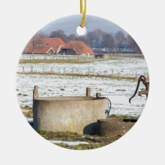Water pump and well in winter snow landscape round ceramic ornament