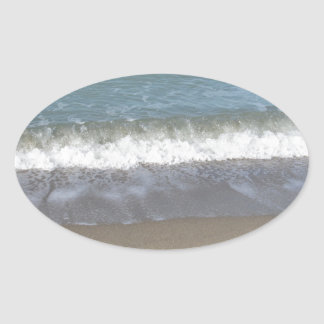 Wave of the sea on the sand beach oval sticker