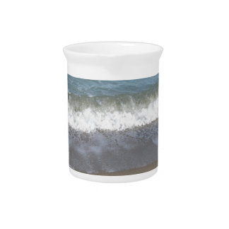 Wave of the sea on the sand beach pitcher
