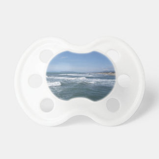 Waves of the sea on the sand beach pacifiers